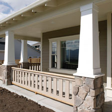 front porch columns with a wood railing systems